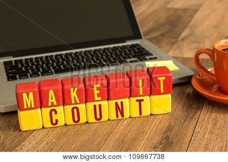 Make It Count written on a wooden cube in a office desk
