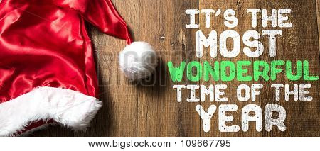 It's the Most Wonderful Time of the Year written on wooden with Santa Hat