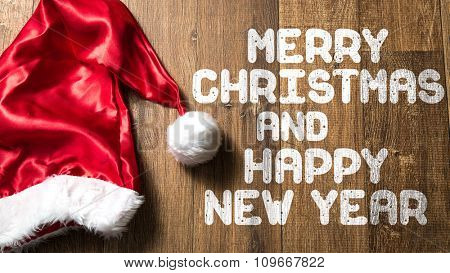 Merry Christmas and Happy New Year written on wooden with Santa Hat