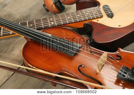 Electric guitar, violin, and headphones on wooden background
