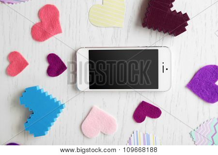 Smart phone with blank screen and hearts on wooden table