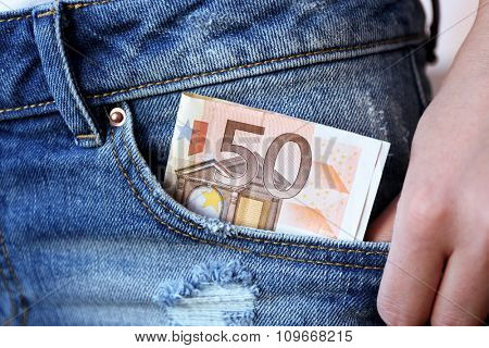 Euro banknotes in jeans pocket closeup