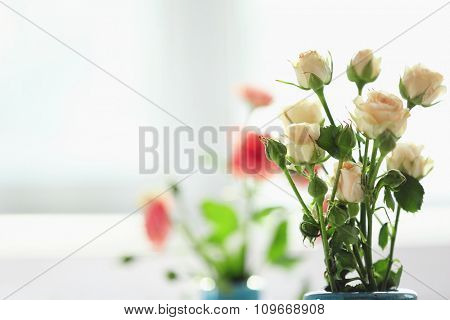 Beautiful spring flowers in vase on window background