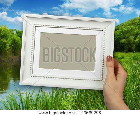 Wooden frame in beautiful woman hands on the background creek in the forest