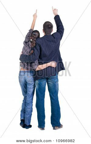 Young Couple Pointing At Wall. Rear View