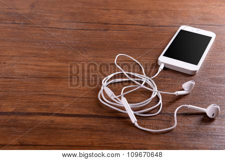 White cellphone with headphones on varnished wooden background
