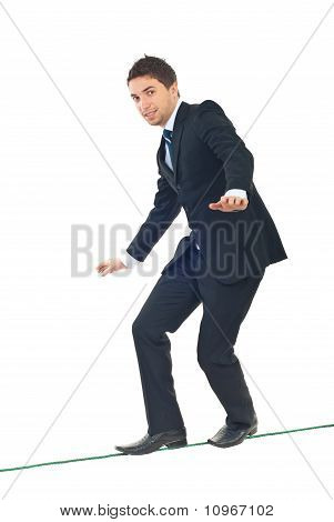 Young Businessman Walking  On Tightrope