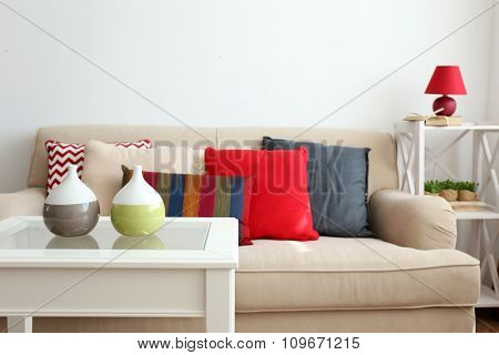 Beige sofa with beautiful pillows and decorative vases on the table in front of it in the room