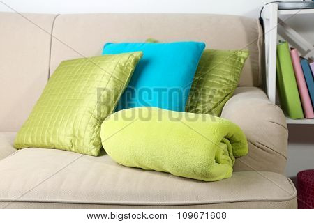 Colorful pillows on sofa, close-up, on home interior background