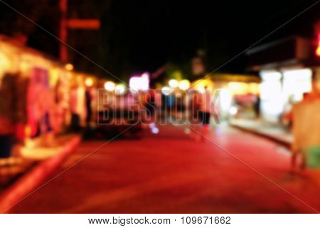 People walking on entertainment street in the evening, unfocused