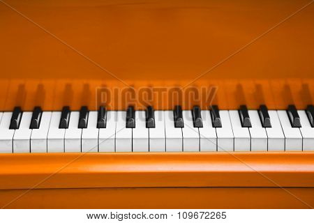 Piano keys of orange piano close up