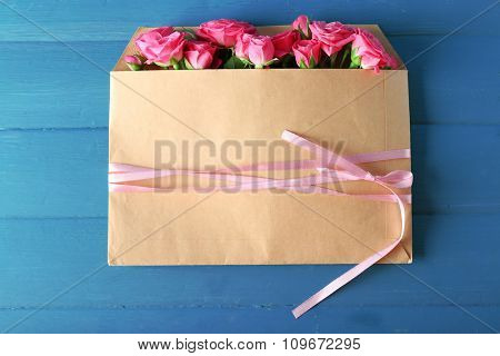 Beautiful roses in envelope on wooden background