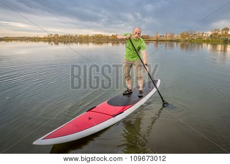 senior male paddler on a paddleboard, lake in Colorado with a fall scenery and dark clouds