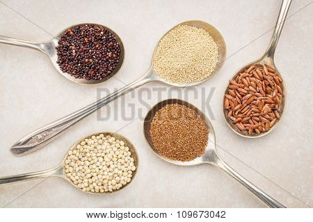 gluten free grain )black quinoa, amaranth,brown rice, teff and sorghum) on old metal tablespoons against ceramic tile