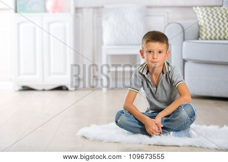 Little boy sitting on carpet, on home interior background