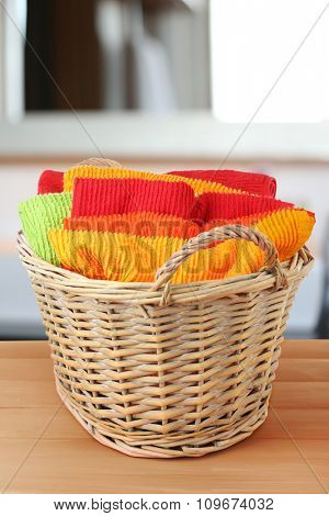Colorful towels in basket on table indoors