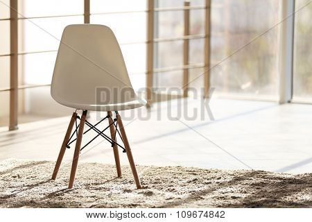 White modern chair in lighted room, on window background