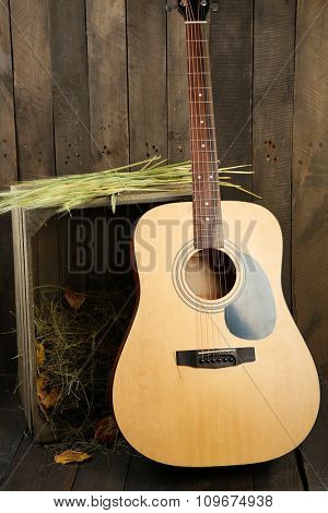 Acoustic guitar against box with hay on wooden background
