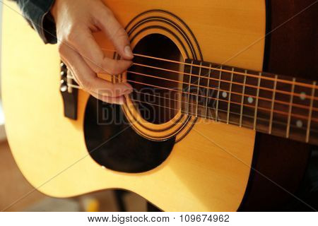 Close up view on musician playing guitars near window