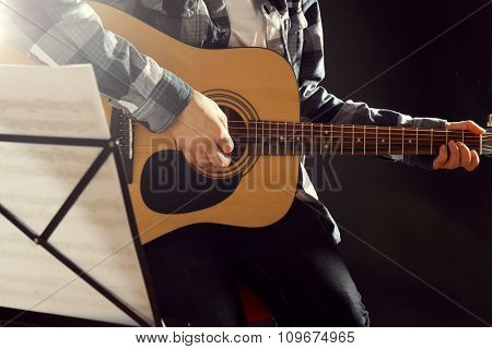 Musician plays guitar on black background in studio with musical notes holder, close up