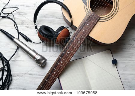 Acoustic guitar, headphones, opened notebook and microphone on wooden background, close up