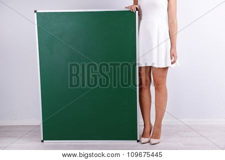 Woman in white dress with green blackboard on grey background, close up