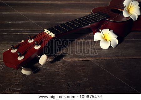 Part of Hawaiian acoustic guitar and flowers on dark wooden background