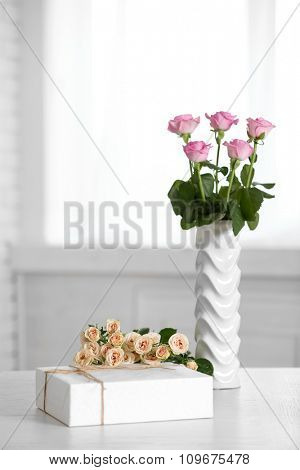 Composition of cute gift boxes and roses on white table
