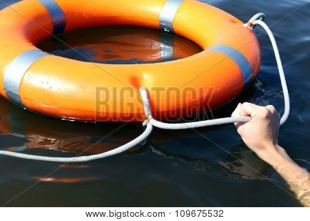 Hand holds a cord of a life buoy