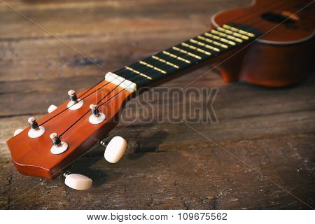 Part of beautiful Hawaiian acoustic guitar on dark wooden background