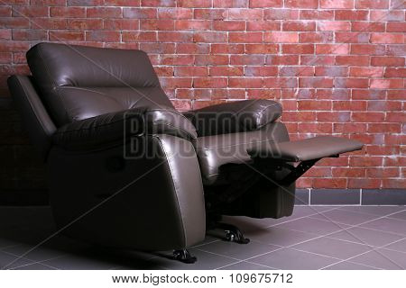 Comfortable brown leather sofa against a brick wall in the room