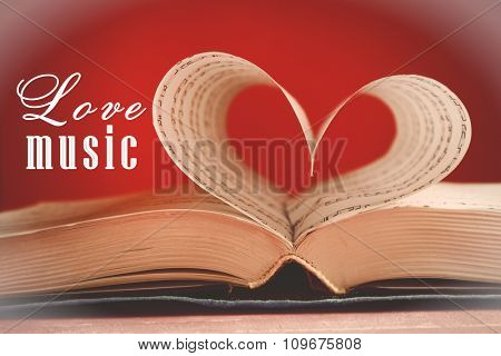 Book pages curved into heart shape on pink background