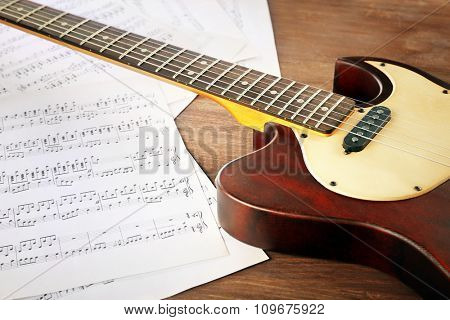 Electric guitar with music notes on wooden table close up