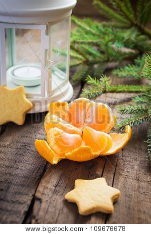 Tangerine peel, lantern, Christmas cookies and spruce branches.