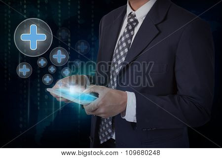 Businessman hand touch screen plus icons on a tablet.