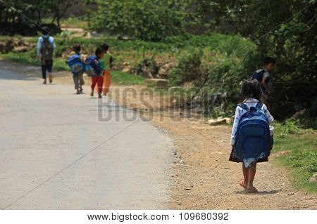 Schoolkids walking to school on a country road under the sunlight