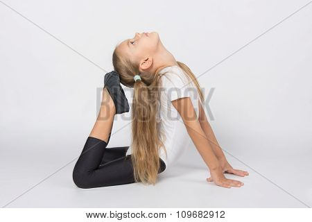 Girl Gymnast Performs Exercises Toes Touching Head