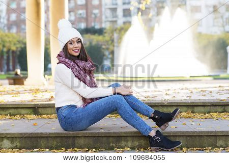 Beautiful Smiling Woman With And Scarf Cap Sitting On Stairs Outdoor.