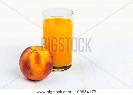 Glass with peach juice and ripe peach