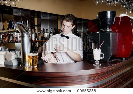 Young Handsome Bartender Working  In Front Of The Bar.