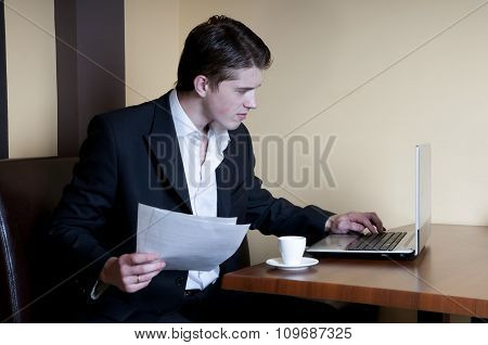 Man with documents sitting at the table in a cafe with a laptop