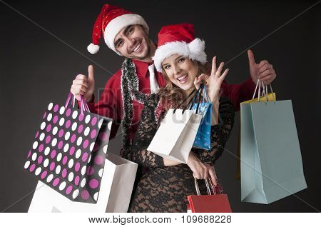 Happy Young Couple   With Shopping Bags Wearing Santa Hat. Christmas Discounts.