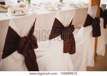 Row of wedding chairs with brown ribbons.