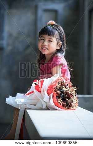 Toothy Smiling Face Of Asian Kid Happiness Emotion And Dry Flowers Bouquet Beside