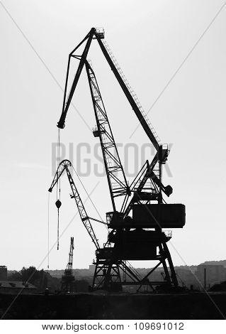 Silhouettes Of Industrial Port Cranes. Danube River