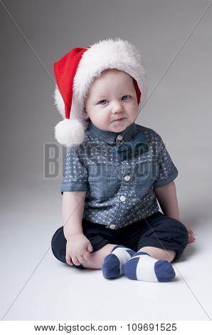 Smiling baby boy wearing santa hat and denim shirt