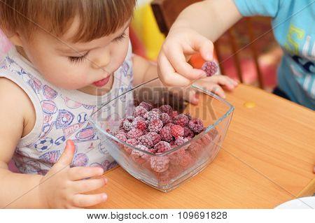 Childs Eating Quick-frozen Raspberries