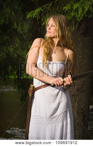 Beautiful Young Girl In White Dress Holding A Medieval Sword