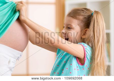 surprised kid looking at pregnant mother belly