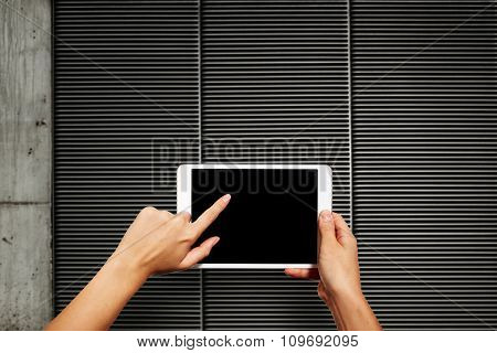 Woman Hands Holding Electronic Tablet Pc With Blank Screen. Isolated Against Texture Wall Background